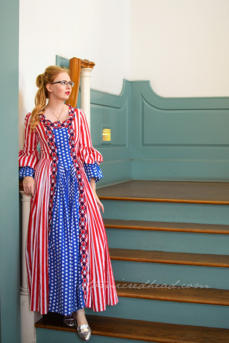 Standing inside Independence Hall, white walls, with mint green trim and warm hardwood floors, wearing a dress made of red and white stripe fabric and blue with white star fabric, done in the 18th century style.