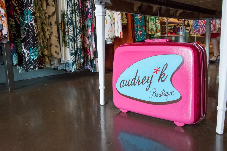 "Inside Audrey K, fanciful dresses with a retro flair, her logo, a blue boomerang with ""audrey k boutique"" inside."