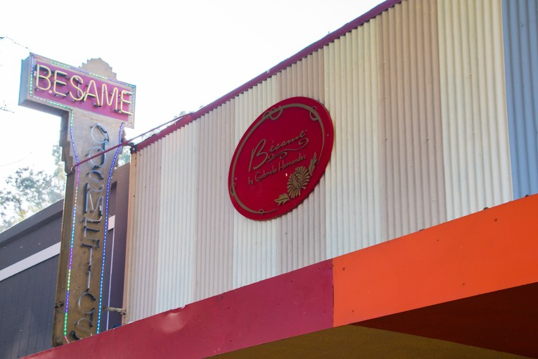 "Sign for Besame Cosmetics. A bright red oval, reading ""Besame Cosmetics"" accompanied by neon reading the same."