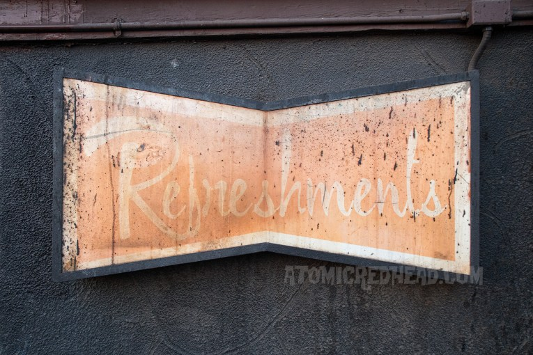 "An old faded sign reads ""Refreshments"" in a lovely retro script."