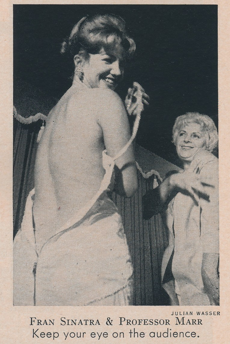 Stripper Fran Sinatra is instructed by Sally Marr in removing her dress.