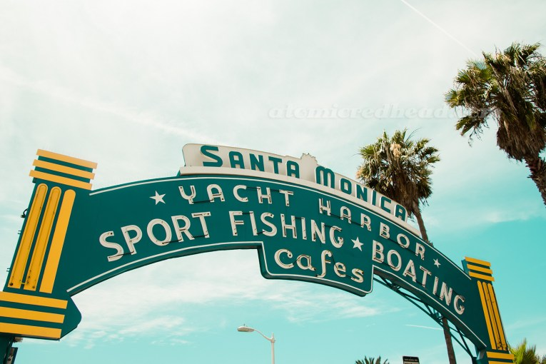 "Neon arch above the pier, reading ""Santa Monica Yachy Harbor, Sport Fishing, Boating, Cafes"""