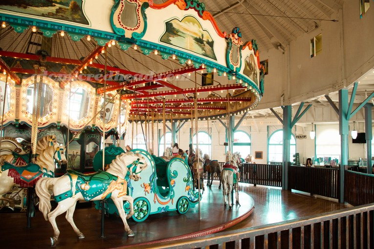 The carousel inside the Hippodrome, horses of a variety of colors, a sleigh painted turquoise also sits upon the carousel.