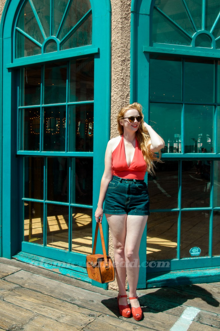 Me outside the Hippodrome, wearing a red halter top, dark blue jean shorts, red platform shoes, and a tooled leather purse.