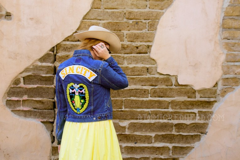 """Inspired by the Sweetheart of the Rodeo, a cream cowboy hat, pink and white gingham peasant top, butter yellow skirt, and cowboy boots, plus a jean jacket featuring patches reading """"Sin City"""" and the artwork of the album, a cowgirl with a ring of yellow flowers around her."""