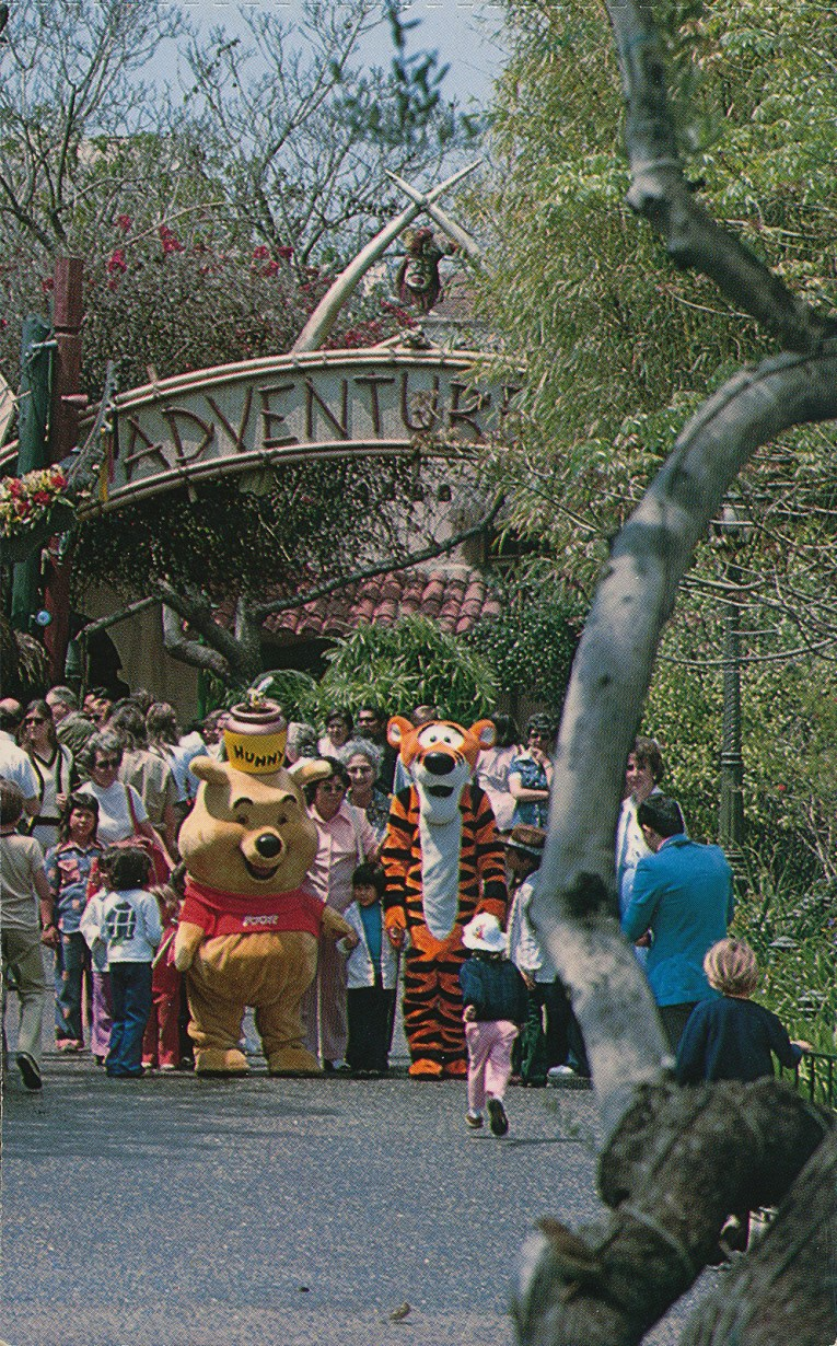 Winnie the Pooh and Tigger walk through the main entrance of Adventureland, which features crossed tusks.