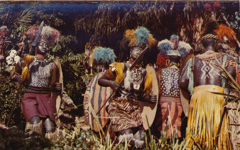 "Colorful ""headhunters"" take part in a dance. Their garb includes necklaces, feathered headdresses, and large painted shields. They also wear face paint."