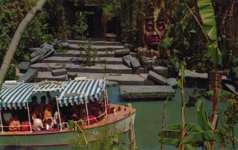 A Jungle Cruise boat sails by the ruins of a temple, including a massive sculpture of a face, overgrown with vines.
