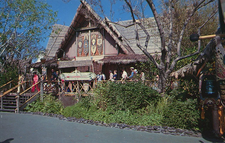 The Enchanted Tiki Room building, with a thatch roof and large tiki paintings on the side.