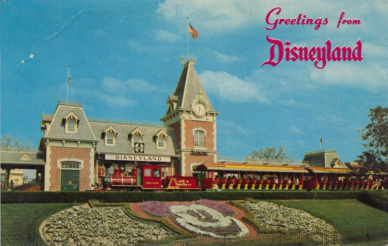 "A look at the Main Street Train Station, with ""Greetings from Disneyland"" across it. A floral version of Mickey greets guests."