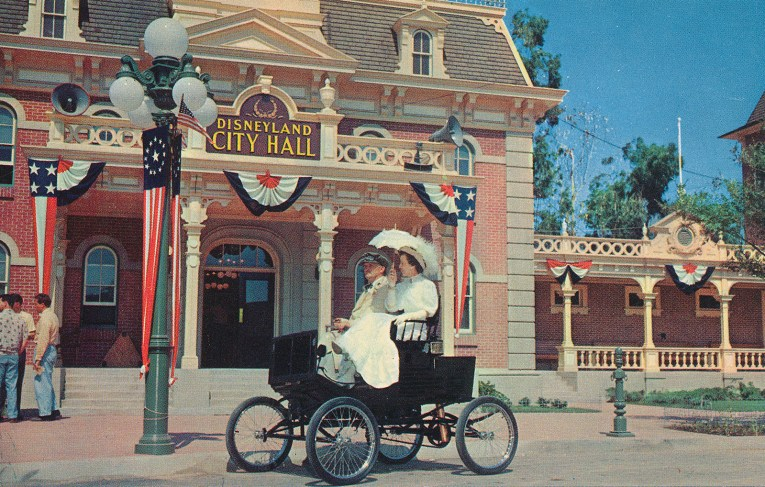 Two Victorian looking ladies ride in a horseless carriage in front of City Hall.