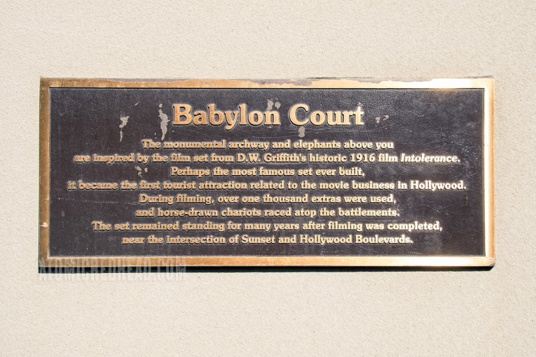 "A plaque reads: ""Babylon Court. The Monumental archway and elephants above you are inspired by the film set from D.W. Griffith's historic 1916 film Intolerance. Perhaps the most famous set ever built, it became the first tourist attraction related to the movie business in Hollywood. During filming, over one thousand extras were used, and horse-drawn chariots raced atop the battlements. The set remained standing for many years after filming was completed, ear the intersection of Sunset and Hollywood Boulevards."