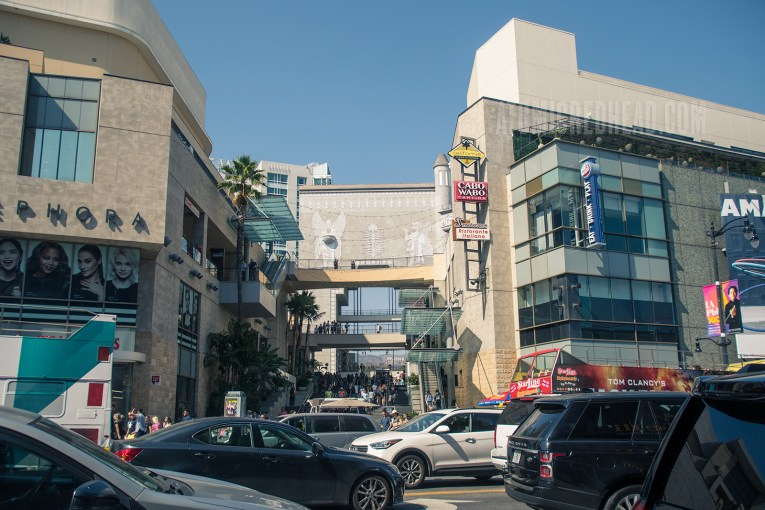 Looking at the shopping center from across the street. Modern looking buildings flank a stairway leading up toward the Babylonian arch/bridge.