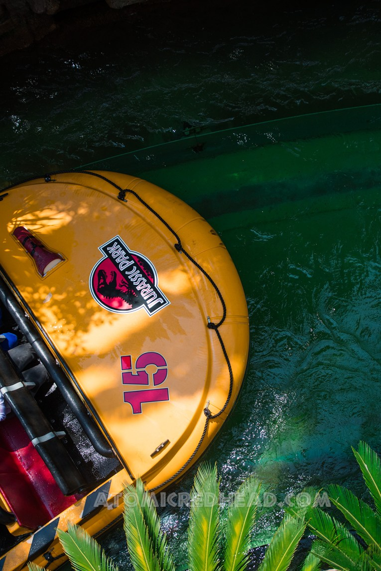 Looking down upon the boats as they glide by, they are yellow with red seats and feature the Jurassic Park logo.