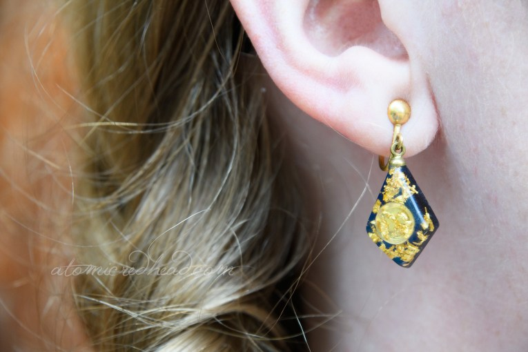 Close-up of my earrings, an elongated diamond shape, with a mini sluice pan and fleck of gold.