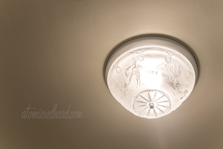 A vintage glass lamp shade features embossed cowboys and cacti.