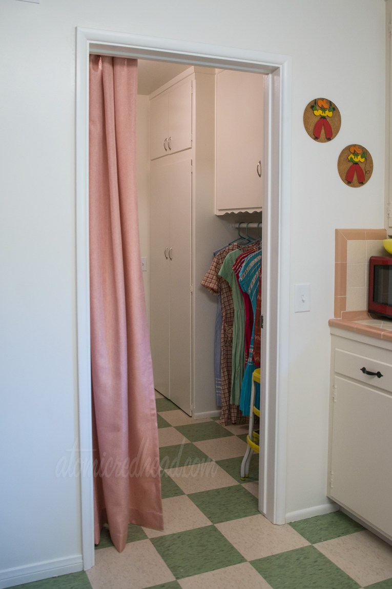 A look into the laundry room from the kitchen. Green and pale yellow check flooring extend into the laundry room. Pale coral curtains hang in the doorway to the left, and just peeking from the laundry room a clothing bar hold clothing that is hanging to dry.