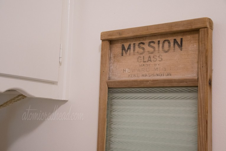 "A close up of the vintage washboard, made of wood and glass, reads ""Mission Glass"" across the top in black letters."