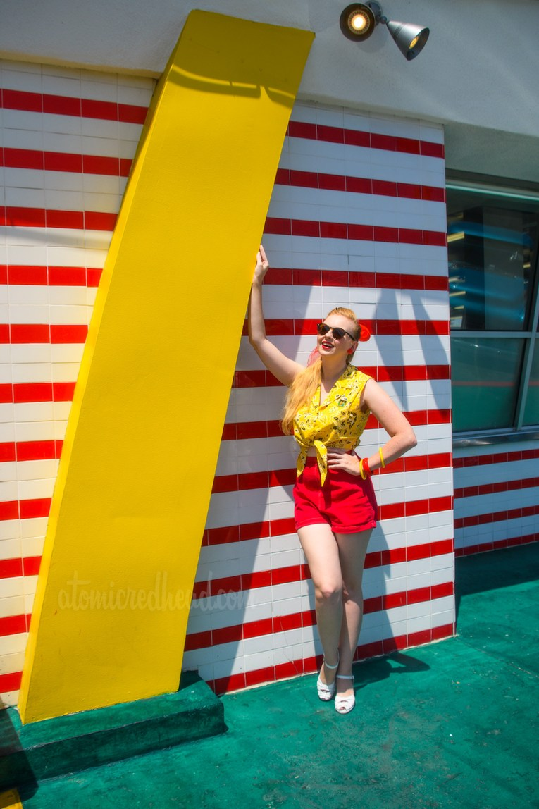 Me, standing outside McDonald's with it's red and white tile and yellow golden arch, wearing a yellow bandana print top, red shorts, white shoes and white purse.