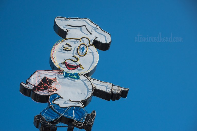Close-up of Speedee, the Hamburger headed chef pointing to the building.