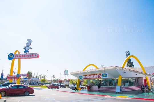 The building - two tall golden arches flank a slanted flat roof, and red and white tile wrap around the bottom. Walls of glass allow guests to walk up to the window and place their orders. The Speedee sign to the left.