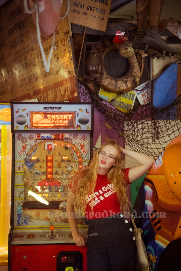 """Inside the Redondo Fun Factory - wearing a vintage red shirt reading """"Have a Coke and a smile"""" and wide leg blue jeans. An 80s basketball game in the background."""