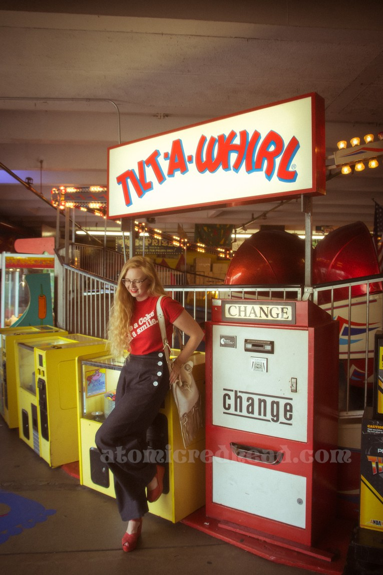 "Inside the Redondo Fun Factory - wearing a vintage red shirt reading ""Have a Coke and a smile"" and wide leg blue jeans. Leaning against the Tilt-a-Whirl."