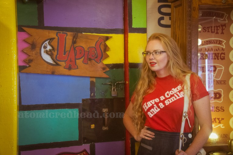 """Inside the Redondo Fun Factory - wearing a vintage red shirt reading """"Have a Coke and a smile"""" and wide leg blue jeans. Leaning against a Love Tester and the Ladies Room next to it, with a sign featuring a crescent moon and """"Ladies"""" written in red script."""