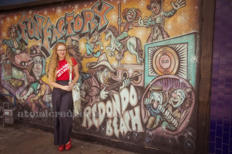 """Outside the Redondo Fun Factory - wearing a vintage red shirt reading """"Have a Coke and a smile"""" and wide leg blue jeans. In the background an airbrush painting of clowns enjoying games and rides."""