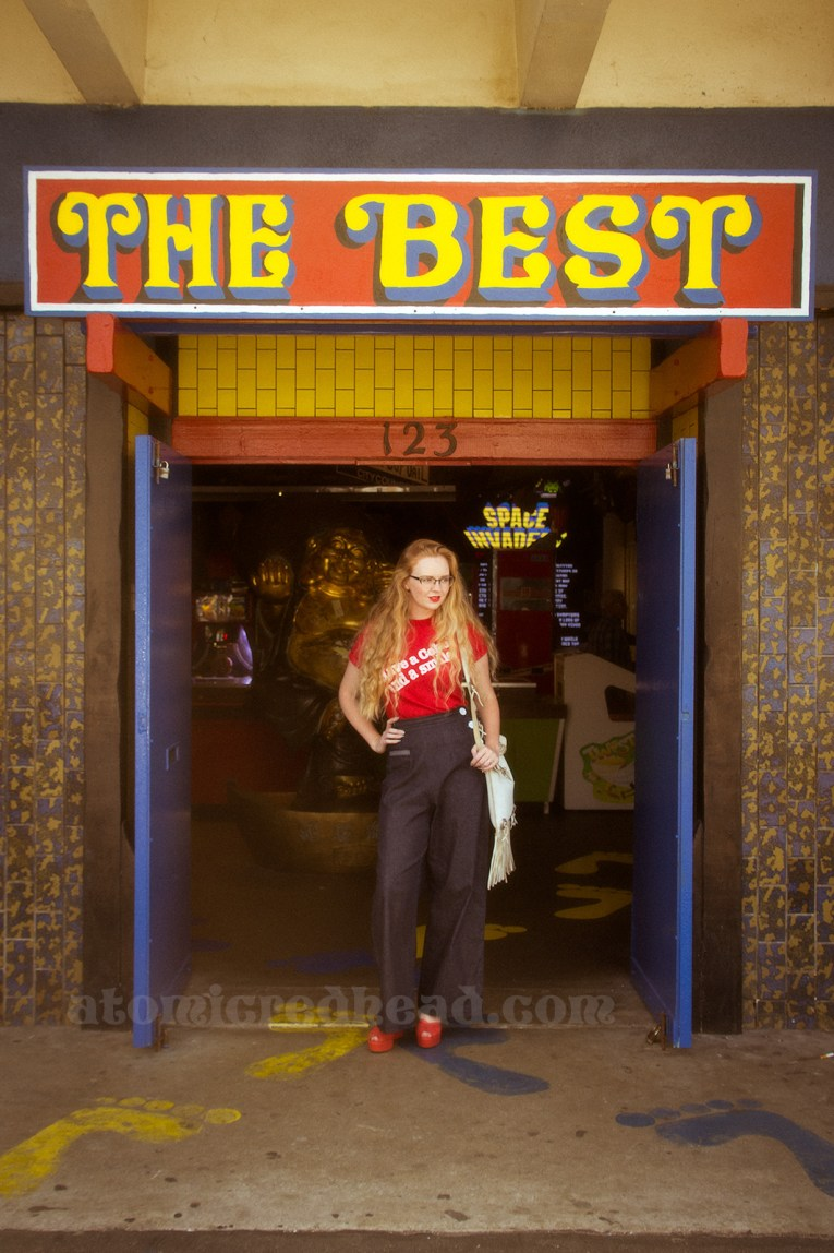 """Standing in the doorway of the Fun Factory under a giant red and yellow sign reading """"THE BEST"""""""
