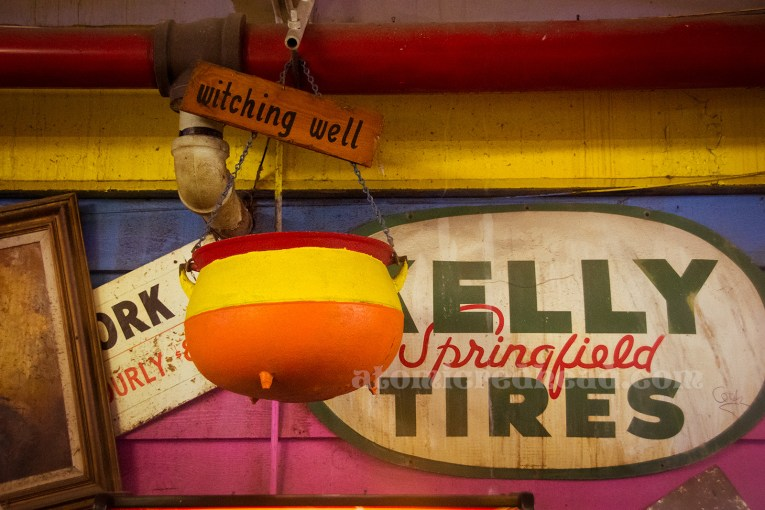 "A red, yellow, and orange painted cauldron hangs above, a sign reading ""Witching Well"" is attached."