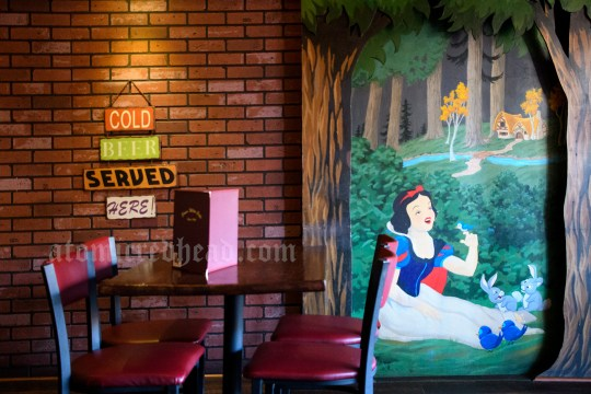 """To the right a mural of Snow White seated in the forest, with bunnies and birds around her. To the left a brick wall and a sign reading """"Cold Beer Served Here."""""""