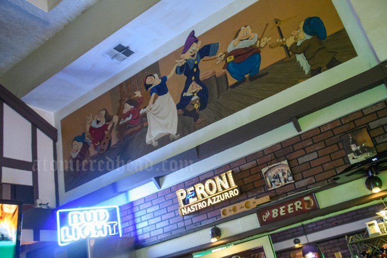 Above the bar, various beer signs, above those a mural of Snow White dancing with the seven dwarves.