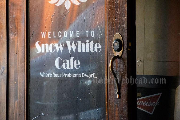 "Script on the door to the cafe reads ""Welcome to Snow White Cafe Where Your Problems Dwarf."""