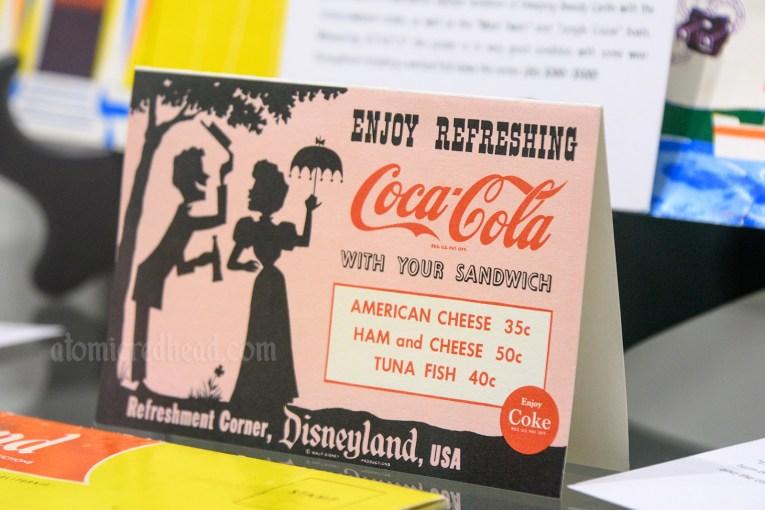 Coca-Cola Refreshment Corner menu, featuring illustration of a gay 90s couple.