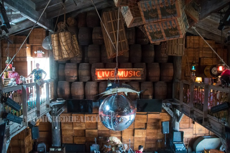 """A view from above, wooden barrels line the wall, with neon reading """"Live Music"""" and below that a large blue marlin hangs. In the center a massive disco ball. Also hanging from the ceiling are multiple boxes, some in large nets."""