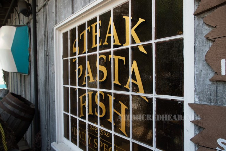 "The window outside reads ""Steak Pasta Fish"" in gold letters."