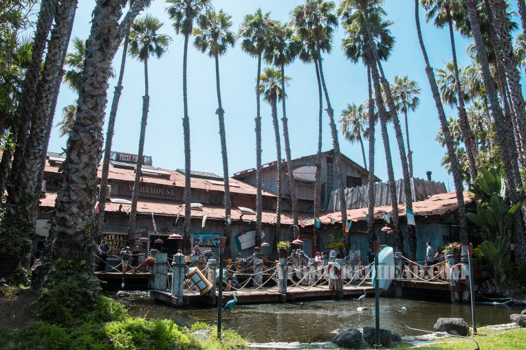 The outside of the Warehouse, a massive, distressed wooden structure, with a faux pier over a manmade lake, and tall palm trees loom over the building and pond.