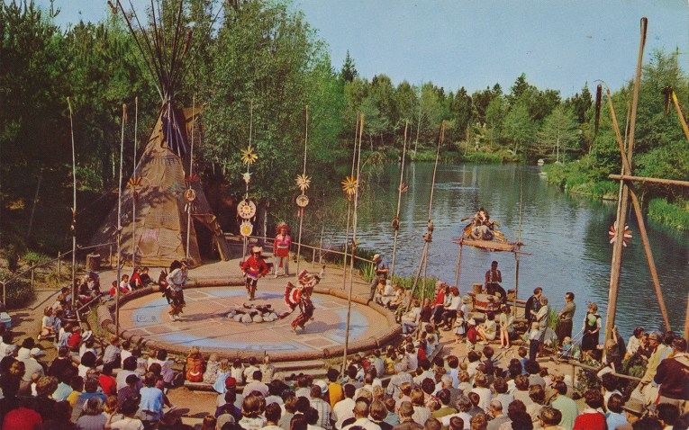 An Indian Dance Circle, with dancers and guests watching, along the banks of the Rivers of America.