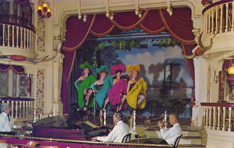 Inside the Golden Horseshoe Saloon, red velvet curtains with gold fringe trim. Can-Can girls in costume, each one wears a different colors, one in green, another in blue, pink, and the last in red.