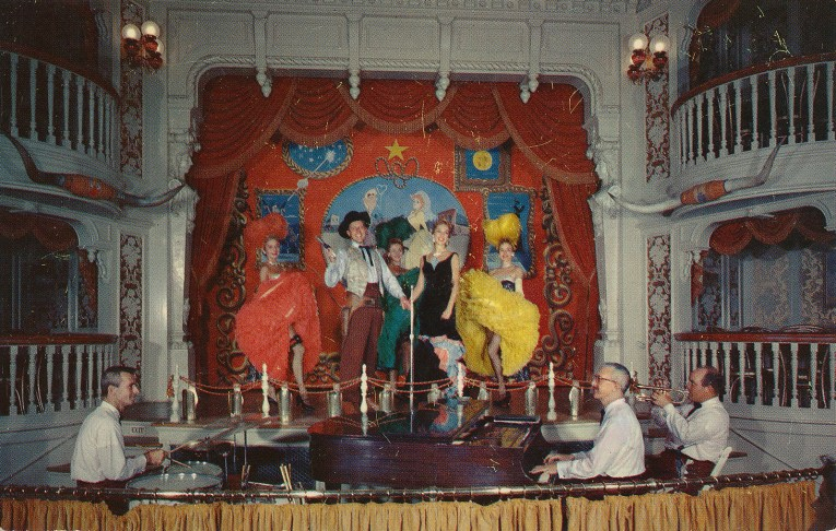Inside the Golden Horseshoe on stage, red velvet curtains with gold fringe. A can-can girl in red stands next to a cowboy, another can-can girl in green stands to him. Next to a singer in a black slinky dress, and finally on the far right another can-can girl in a yellow outfit.