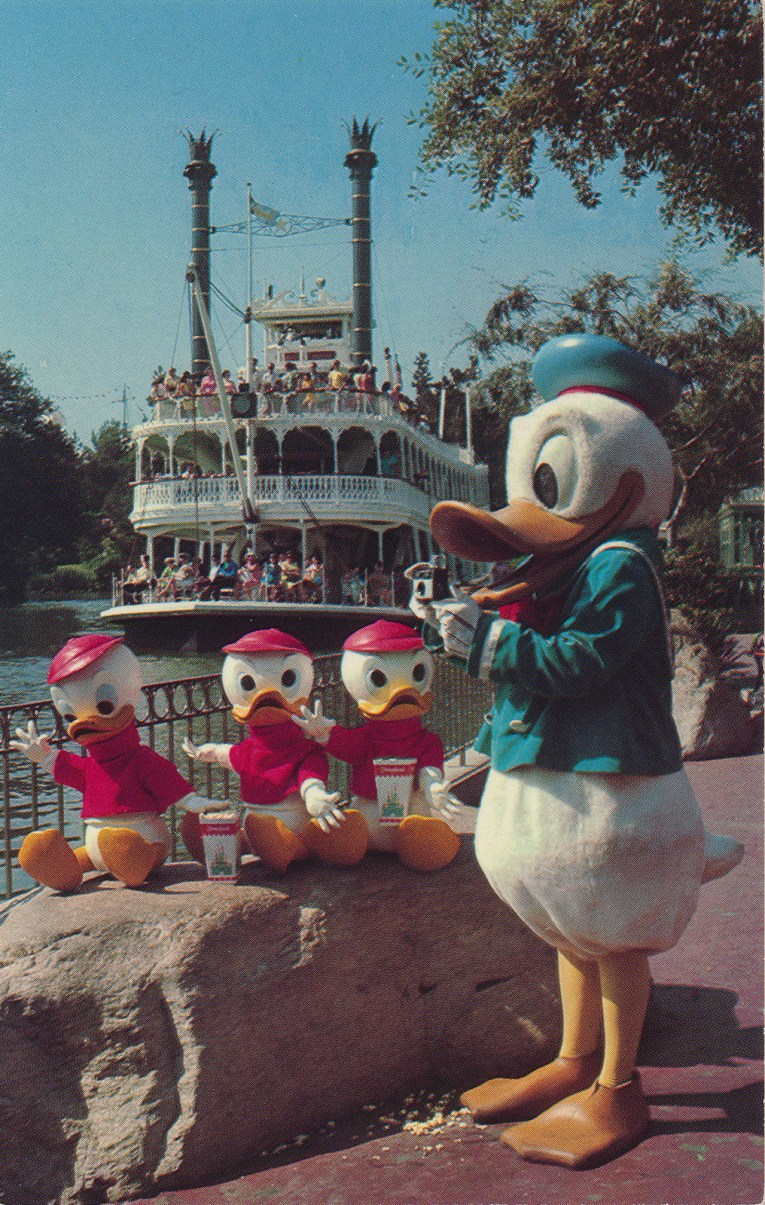 Donald Duck stands on the banks of the Rivers of America with his nephews, Huey, Duey, and Louie. The Mark Twain sits in the water in the background.