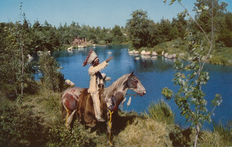 A Native American chief sits atop a horse and waves to passers by along the shores of the Rivers of America.