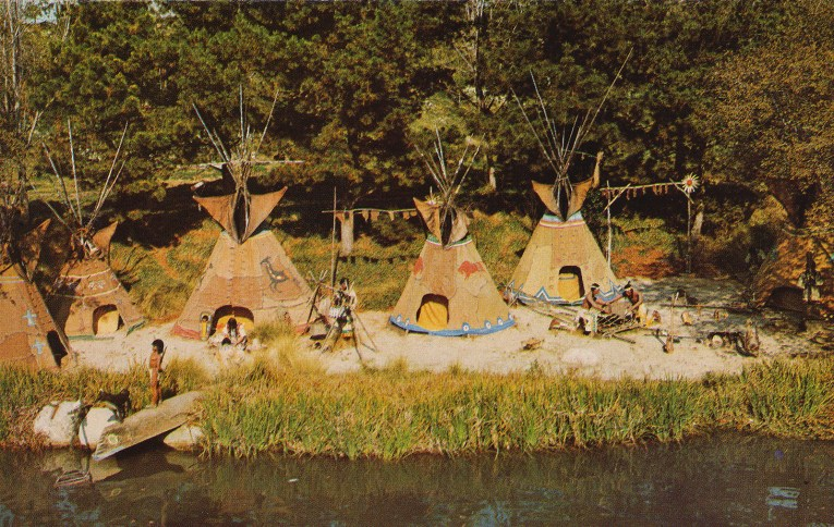 A trio of tipis and Native Americans rest along the banks of the Rivers of America.