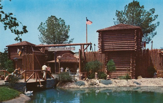 "The entrance to Frontierland, which looks like an old fort, made of logs, a large sign reading ""Frontierland"" hangs over the gateway."