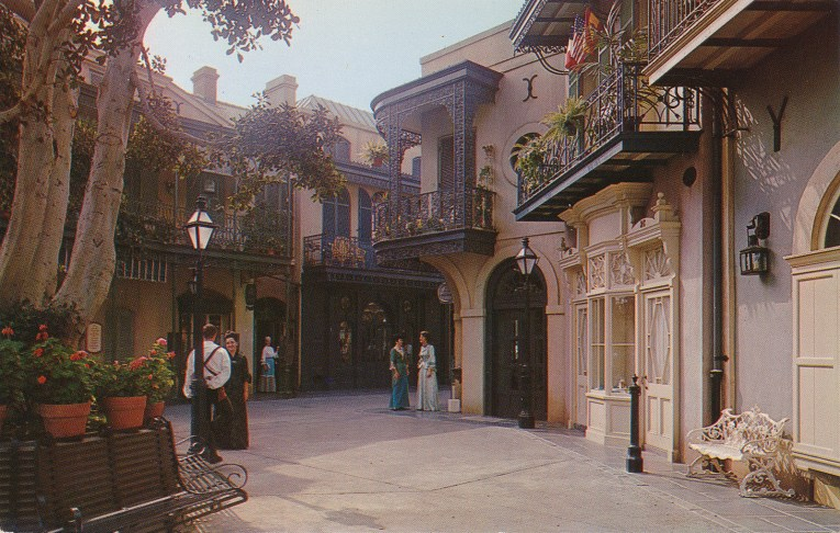 An alleyway through New Orleans Square, warm stone walls and curly wrought iron work in balconies above.