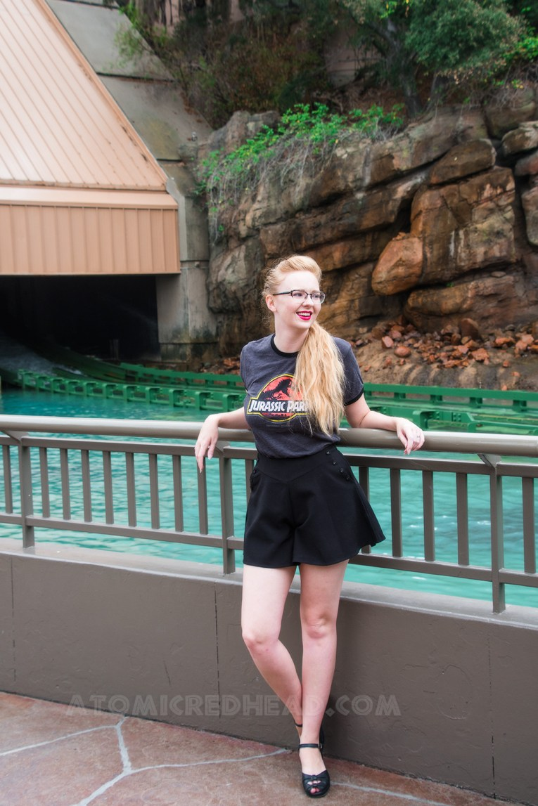 Standing just outside the waterfall lagoon wearing a green t-shirt featuring the yellow and red Jurassic Park logo, and black shorts.