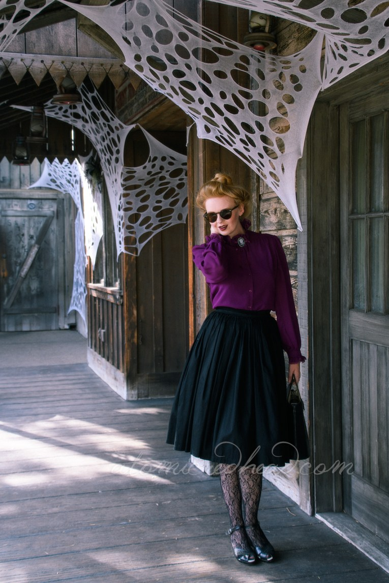 Western style wooden buildings go toward the distance, ending in a wall covered in various brands, myself standing in front, wearing a long sleeve purple, Victorian style shirt, with a black and white cameo, and a black full skirt, net style tights with a floral design and black shoes. My hair is piled atop my head in a Gibson Girl style.