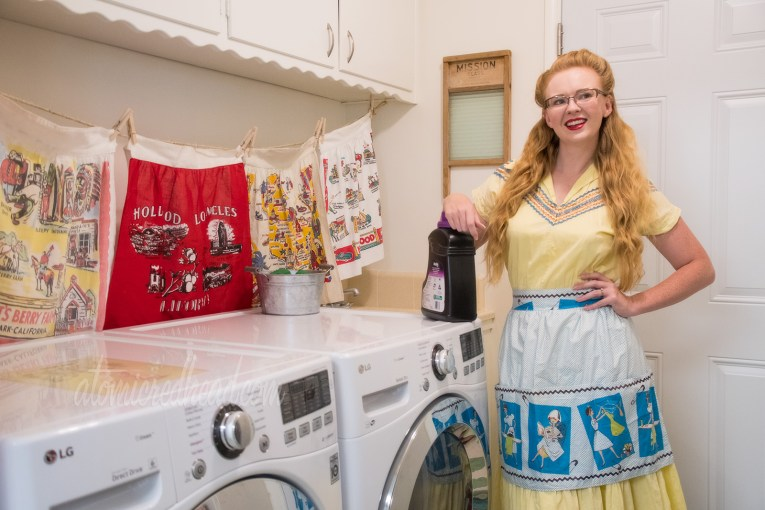 Standing in the laundry room, wearing a yellow dress with blue trim and a blue and white apron featuring a cartoon illustration of a woman doing laundry and getting her hair done.