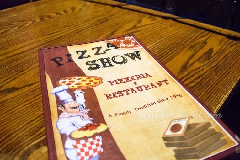 Pizza Show menu, featuring an illustration of a chef holding pizza and spaghetti, a stack of pizza boxes sit in the lower right of the menu.